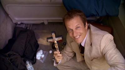 Cotton Marcus (Patrick Fabian) proudly displays the powerful crucifix he uses during exorcisms.