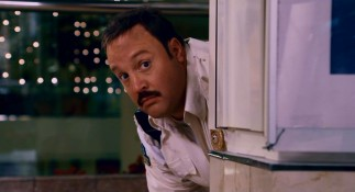 Paul Blart peers out from behind a mall directory, slowly moving into reluctant action hero mode.