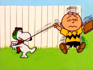 "Flying Ace Snoopy reminds Charlie Brown who's in control with a ""play dead, then yank the leash"" trick."