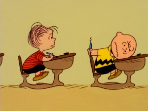 Linus sees Charlie Brown slam his head down on his desk after failing to attract the attention of the Little Red-Haired Girl with some suave pen-sharpening.