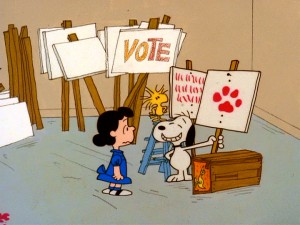 "Snoopy and Woodstock proudly show campaign manager Lucy their sign artwork in ""You're Not Elected, Charlie Brown."""