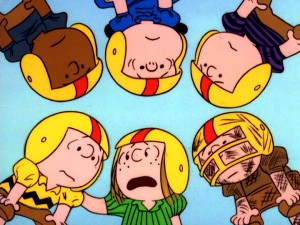 In a team huddle, player-coach Peppermint Patty tells placekicker Chuck the plan, while teammates Franklin, Lucy, Shermy, and Pig Pen listen on.