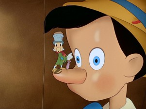 Our guide Jiminy Cricket, the original and unsurpassed comic sidekick, perches upon Pinocchio, still a mouthless puppet.