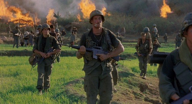 "Having carried out their orders to torch the farm village, the soldiers of Bravo Company (including John C. McGinley) move on to their next objective in ""Platoon."""