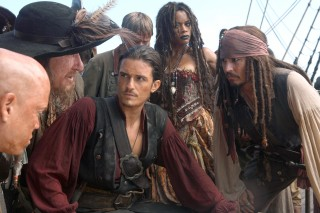 Will Turner (Orlando Bloom), Tia Dalma (Naomie Harris), and Captain Jack Sparrow (Johnny Depp) stop, collaborate, and listen, respectively.