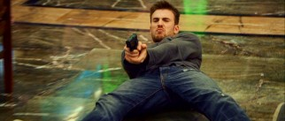 Nick Gant (Chris Evans) slides back and shoots, while his target deflects the bullets with his bare hands.