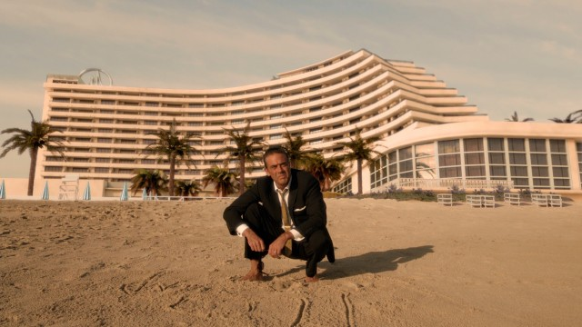"Ike Evans (Jeffrey Dean Morgan) draws in the sand and looks out into the ocean in front of his Miramar Playa hotel in what would be the final shot of ""Magic City."""