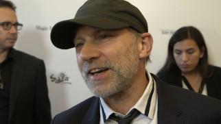 Simon McBurney uses a plain baseball cap to cover up his unusual balding for the red carpet of Magic in the Moonlight's LA premiere.