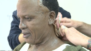 "Idris Elba is creepily fitted with a Mandela face prosthetic in ""Prosthetics & Costuming."""