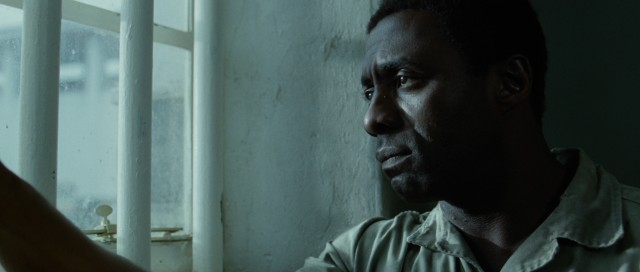 "A glum Nelson Mandela (Idris Elba) looks out his jail cell's window in ""Mandela: Long Walk to Freedom."""
