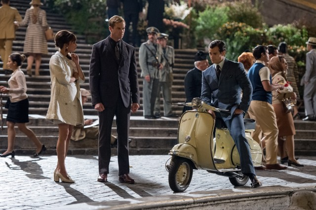 Napoleon Solo (Henry Cavill) coaches Gaby Teller (Alicia Vikander) and Illya Kuryakin (Armie Hammer) on how to act like an ordinary engaged couple.