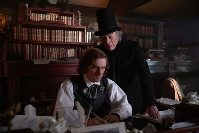 "Ebenezer Scrooge (Christopher Plummer) materializes and stands over Charles Dickens (Dan Stevens) in ""The Man Who Invented Christmas."""