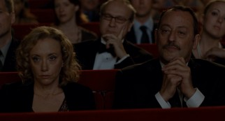 Joan (J. Smith-Cameron) and Ramon (Jean Reno) go to the opera on a date.
