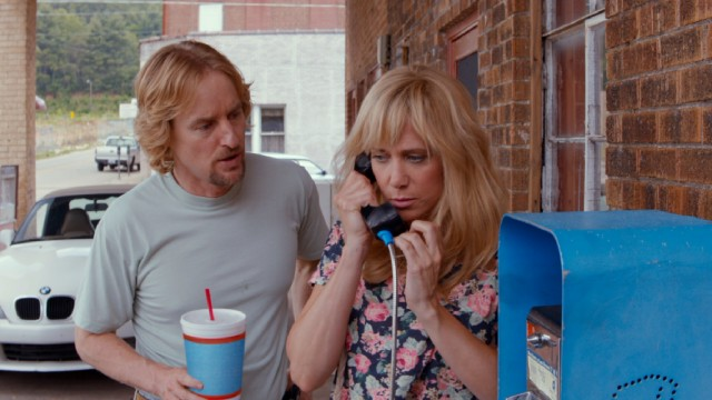 Steve Chambers (Owen Wilson) listens in while Kelly Campbell (Kristen Wiig) catches up with the Mexico-fled David using something called a pay phone.