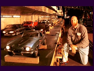 A crew member proudly poses as a giant next to miniature cars in a production photos gallery still.