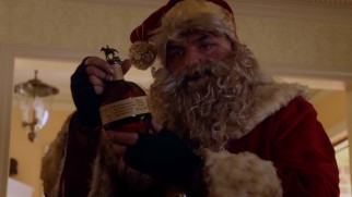 Hobo Santa (Oliver Platt) truly does prefer bourbon to cookies and milk.