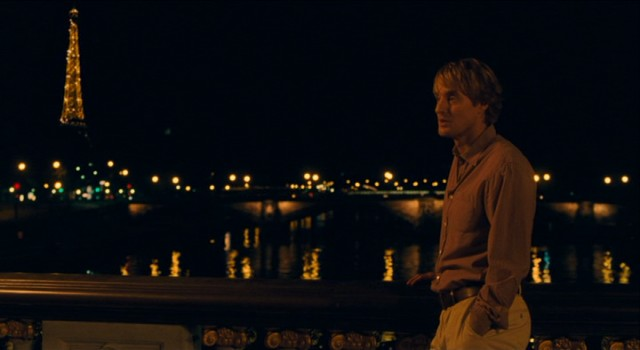 "The Eiffel Tower lights up behind Gil Pender (Owen Wilson) during another magical ""Midnight in Paris."""