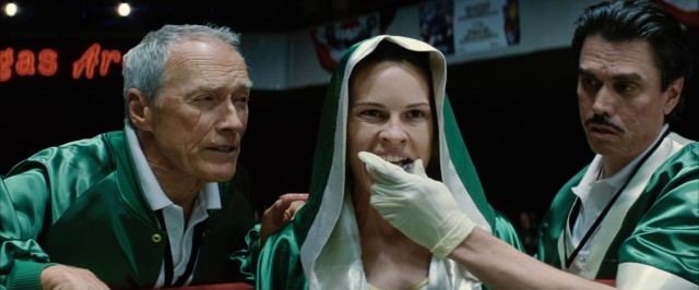 Frankie Dunn (Clint Eastwood) looks on as Maggie Fitzgerald (Hilary Swank) gets her mouth guard put in by an Edward James Olmos-lookalike.