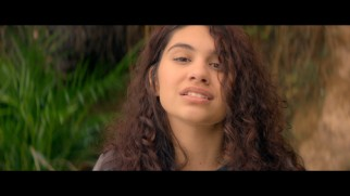 "Alessia Cara sings (and rakes sand) on a beach in the music video for her pop cover of ""How Far I'll Go."""
