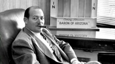 """The Incredible Mr. Lippert"" shows producer Robert L. Lippert poses proudly at his desk, with a cigar in his mouth and ""Baron of Arizona"" ad behind him."