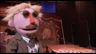 The Muppet version of director James Bobin objects to the curtain's botched title logo in this Easter egg.
