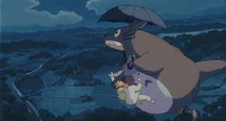 The big gray Totoro lets out a noise as he gives an umbrella ride to four small friends.