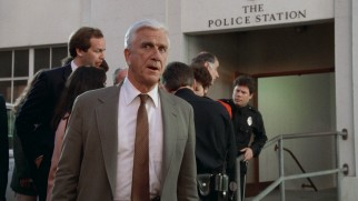 Lieutenant Frank Drebin (Leslie Nielsen) plays it cool after being responsible for his car's downhill roll.