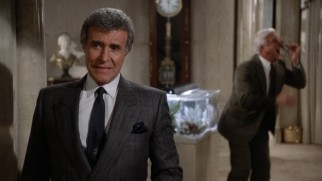 While Vincent Ludwig (Ricardo Montalban) spouts villainy in the foreground, Frank Drebin clowns around with a fishtank piranha out of focus.