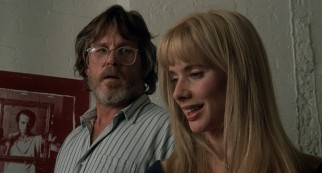 Artist Lionel Dobie's (Nick Nolte) feelings for his young assistant Paulette (Rosanna Arquette) become unrequited as performance artist Gregory Stark (Steve Buscemi) looks on from a wall poster.