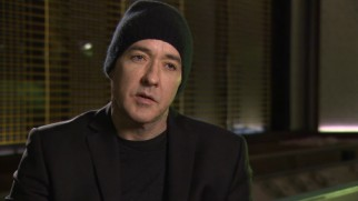 "A beanie keeps John Cusack's head warm as he speaks in ""The Making of 'The Numbers Station.'"""