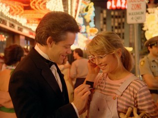 Suave Ray (Raul Julia) hands Frannie (Teri Garr) a matchbook to the club where he is a singer/pianist/waiter.
