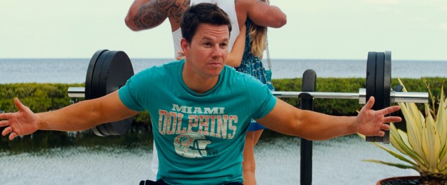 "Sporting a 1990s Miami Dolphins T-shirt, Daniel Lugo (Mark Wahlberg) imparts some questionable wisdom on impressionable neighborhood youths in ""Pain & Gain."""