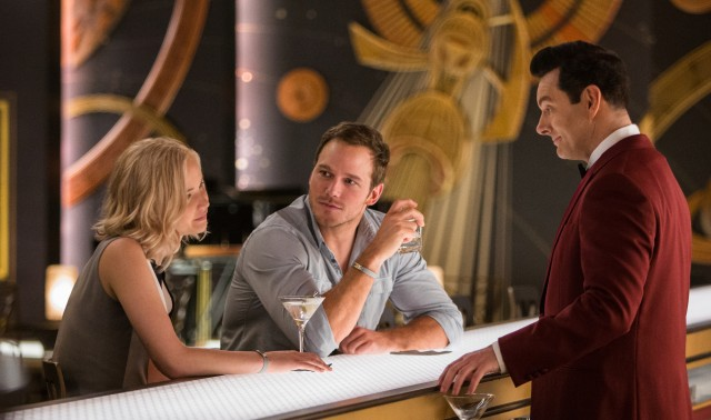Aurora (Jennifer Lawrence) and Jim (Chris Pratt) enjoy drinks and conversation with android bartender Arthur (Michael Sheen).