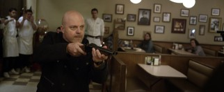 Derrick (Michael Chiklis) calls the shots with a loaded gun and a firm tone to his Cockney accent.