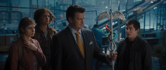 Behind the scenes of his UPS Store, Hermes (Nathan Fillion) shows Annabeth, Tyson, and Percy his staff with snakes and other fantastical things.