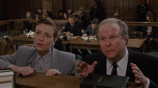 Dueling lawyers (Theresa Russell and Ned Beatty) approach the bench.