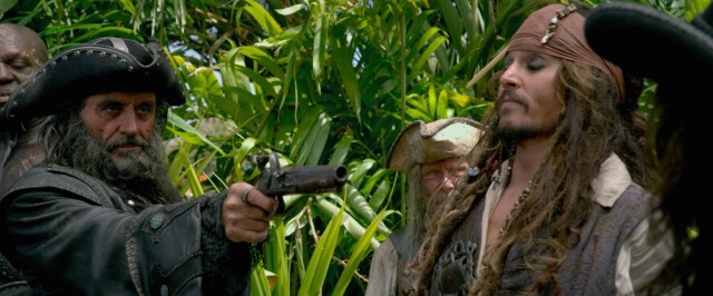 Blackbeard (Ian McShane) orders Captain Jack Sparrow (Johnny Depp) with a gun in his hand.
