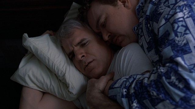 Neal (Steve Martin) and Del (John Candy) awaken to find themselves in an unconscious cuddle in their single-bed Wichita hotel room.