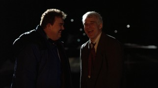 Del and Neal can only laugh and watch as their rented car goes up in flames.