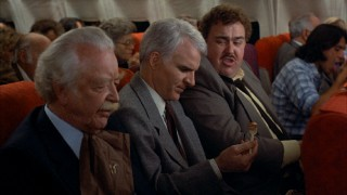 Del shares his knowledge of airline food with Neal in this lone deleted scene.