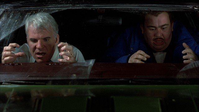 Neal Page (Steve Martin) and Del Griffith (John Candy) pull their fingernails out from the dashboard after a very close call in their rented car.