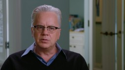 "A white-haired Tim Robbins looks back at ""The Player"" in ""Planned Improvisation."""