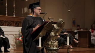 "Per ""his request"", Fred Armisen speaks before the Oregon Episcopalian School Class of 2011 from a podium that looks like he's riding an eagle."