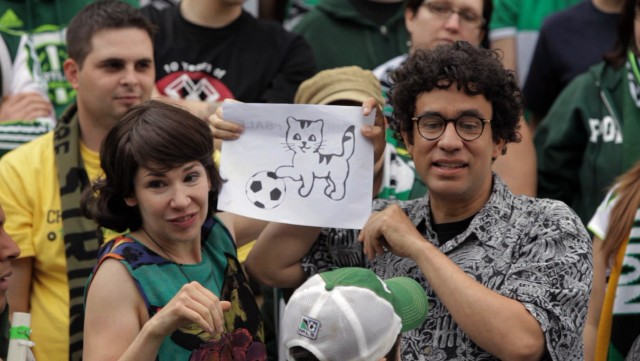 Nance (Carrie Brownstein) and Peter (Fred Armisen) celebrate their first Portland Timbers game with a festive soccer-playing cat banner.
