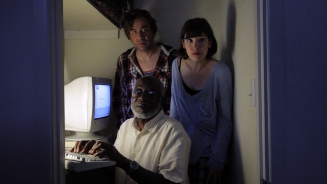 "Doug (Fred Armisen) and Claire (Carrie Brownstein) find a Ronald D. Moore (Henry Cottrell) and commission him to write another ""Battlestar Galactica"" episode, which he does at night in a computer closet."