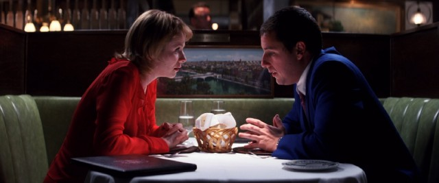Barry (Adam Sandler) leans in to tell Lena (Emily Watson) about his pudding for frequent flier miles plan.