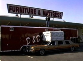 In character as the D & D mattress man, Philip Seymour Hoffman pitches mattresses and takes a fall off the stack of mattresses in this faux commercial.