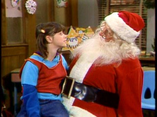 "Punky (Soleil Moon Frye) tells Santa Claus (Henry) what she wants for Christmas in the first half of ""Yes, Punky, There is a Santa Claus."""