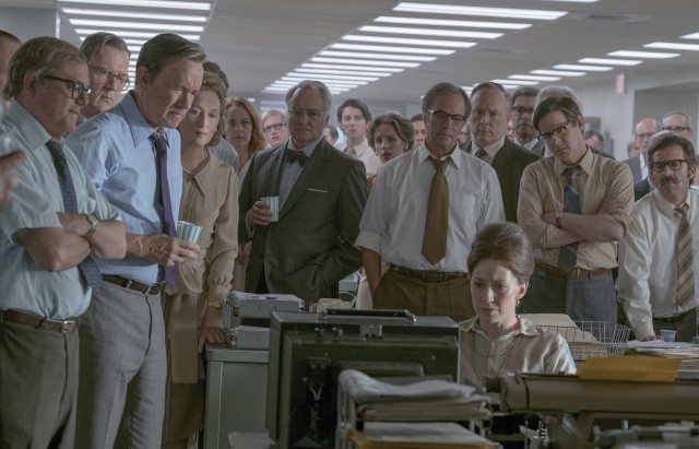 Ben Bradlee (Tom Hanks) and his Washington Post reporters gather around to watch a television news report on actions taken against The New York Times.