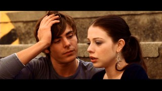 "Since Warner made all ""17 Again"" bonus features exclusive to Blu-ray, we bring you another movie screencap. Here, father (Zac Efron) consoles daughter (Michelle Trachtenberg) on the bleachers while trying to keep incestuous urges at bay."